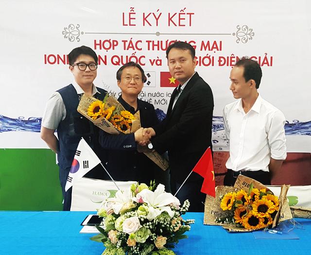 Ông Lê Thành Nhân (Thứ 2 từ bên phải qua) trao hoa chúc mừng hợp tác thành công cho ông Song Dong-Sub (Thứ hai từ trái qua)